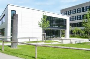 Der moderne Erweiterungsbau des Wilhelm-Hausensteins-Gymnasiums (WHG), an den sich die 1974 erstellte Dreifachturnhalle anschließt, die inzwischen von Grund auf saniert worden ist.