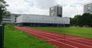 Das Wilhelm-Hausenstein-Gymnasium im Arabellapark aus dem Blickwinkel der Englschalkinger Straße mit Sportplatz, Bestandsgebäude (li.) und der sanierten Turnhalle, die auch als Veranstaltungssaal für bis zu 600 Besucher genutzt werden kann.