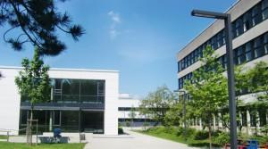 Das 44 Jahre alte Bestandsgebäude des Wilhelm-Hausenstein-Gymnasiums an der Elektrastraße im Arabellapark wird ab Anfang/Mitte 2018 komplett saniert. Im Hintergrund die modernisierte Dreifachturnhalle, links der großzügige neue Ergänzungsanbau.