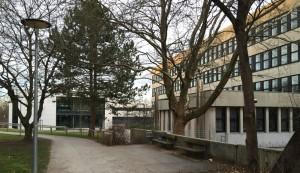Das fast 45 Jahre alte Bestandsgebäude des Wilhelm-Hausenstein-Gymnasiums (WHG) an der Elektrastraße im Arabellapark muss dringend saniert werden. Im Hintergrund der großzügige neue Ergänzungsbau mit sieben Klassenzimmern.