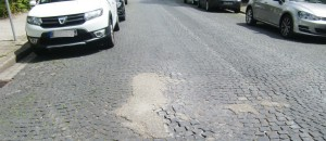 Die Maria-Theresia-Straße Mitte Juni: Mit Teer ausgebesserte Löcher auf der mit Pflastersteinen belegten Fahrbahn hatten das Straßenbild verschandelt.  Foto: hgb