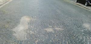 Die Höchlstraße an der Einmündung in die Maria-Theresia-Straße Mitte September: Unansehnlich mit Teer ausgebesserte Löcher in der Fahrbahn.   Foto: hgb