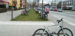 Ein Bild, das ab Sommer der Vergangenheit angehören sollte, wenn die Stadt Fahrradständer installiert hat: An Bäumen angekettete oder will abgestellte Fahrräder bei den Bushaltestellen Zaubzer-/Ecke Richard-Strauss-Straße stadtein- wie auch stadtauswärts.    Foto: hgb