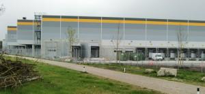 Das graue Amazon-Logistikzentrum mit gelben Streifen an den Hallendachrändern und elf Laderampen an der Grasbrunner Straße im Gewerbegebiet Am Hüllgraben in Daglfing mit. Wann der Auslieferungsbetrieb startet, ist derzeit noch offen.